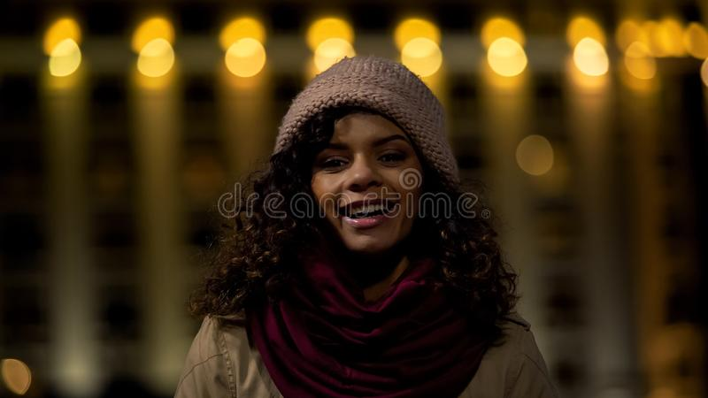 Leuk krullend-haired toevallig meisje die en oprecht bij camera, gelukkige dame stellen glimlachen royalty-vrije stock afbeelding