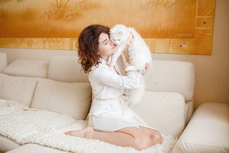 Leuk krullend meisje in een witte zijdepeignoir in de vroege ochtend die met witte pluizige kattenzitting spelen op bank royalty-vrije stock foto