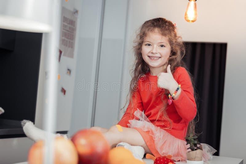 Leuk langharig glimlachend meisje met een armbandzitting op de lijst stock afbeeldingen