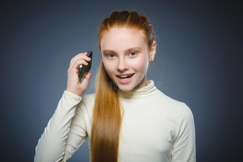 Leuk meisje dat op de celtelefoon spreekt Geïsoleerd op grijs royalty-vrije stock fotografie