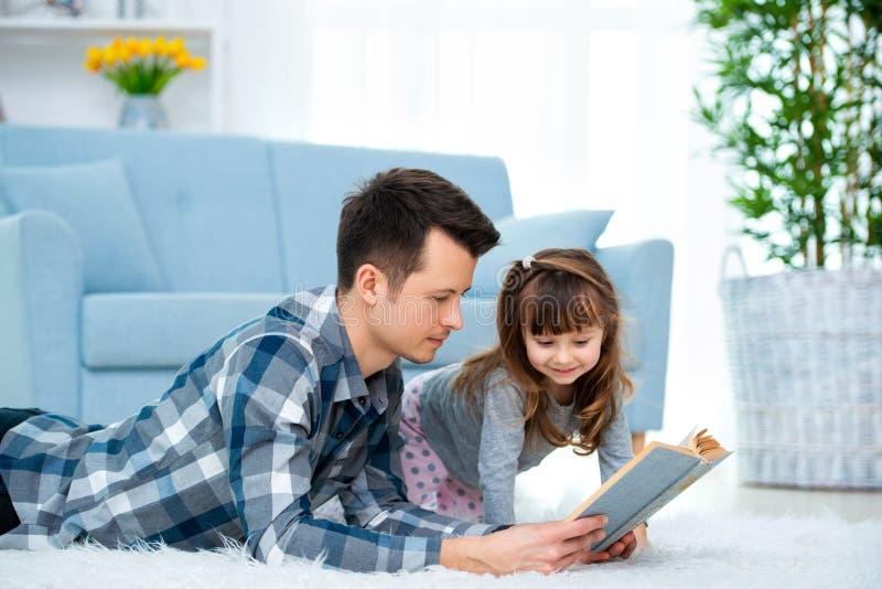 Leuk meisje die aan het sprookje luisteren die van de papalezing op warme vloer samen liggen, het geven het boek van de vaderhold royalty-vrije stock afbeelding