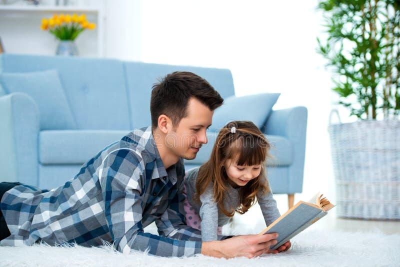 Leuk meisje die aan het sprookje luisteren die van de papalezing op warme vloer samen liggen, het geven het boek van de vaderhold stock fotografie