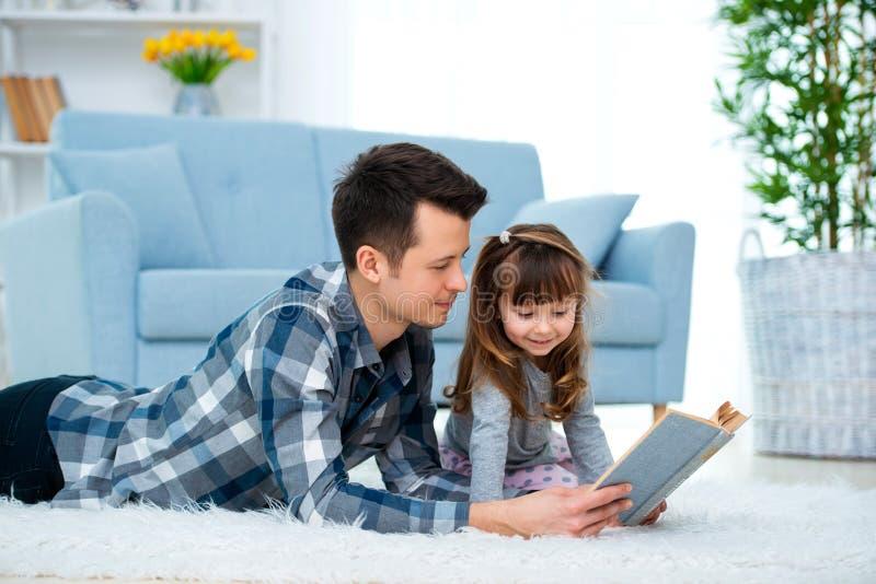 Leuk meisje die aan het sprookje luisteren die van de papalezing op warme vloer samen liggen, het geven het boek van de vaderhold stock afbeeldingen