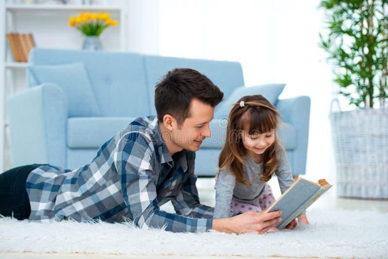 Leuk meisje die aan het sprookje luisteren die van de papalezing op warme vloer samen liggen, het geven het boek van de vaderhold royalty-vrije stock foto