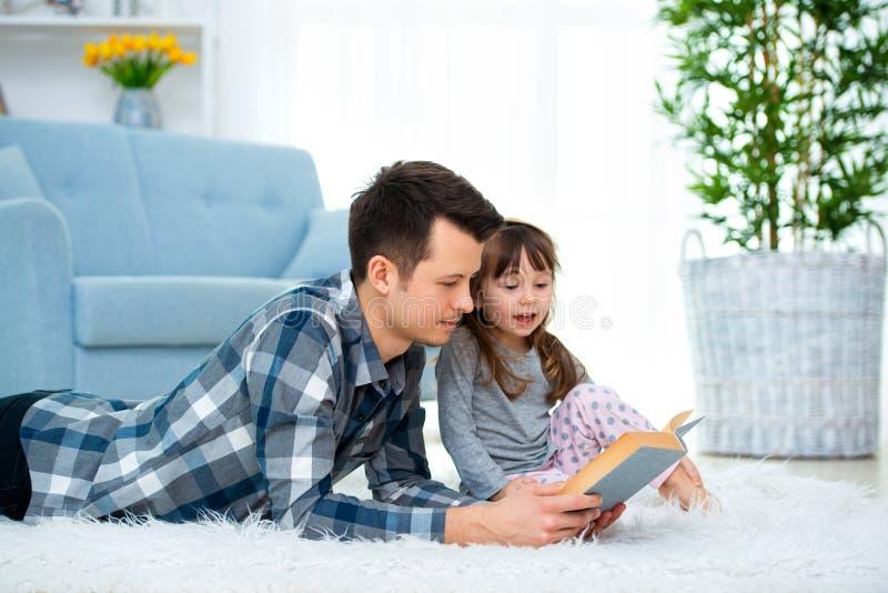 Leuk meisje die aan het sprookje luisteren die van de papalezing op warme vloer samen liggen, het geven het boek van de vaderhold royalty-vrije stock fotografie