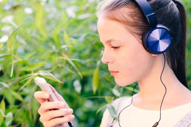 Leuk meisje die aan muziek met hoofdtelefoons luisteren openlucht royalty-vrije stock fotografie