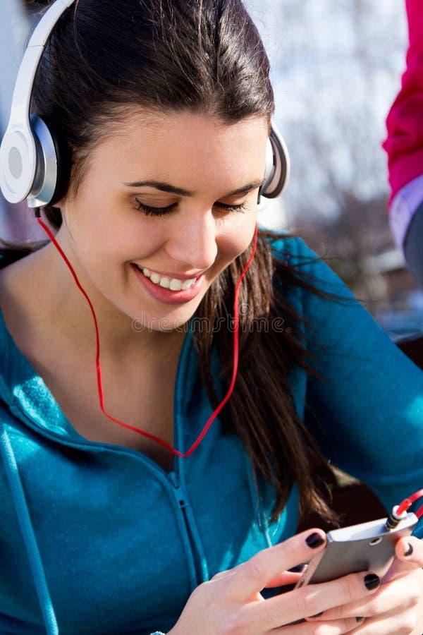 Leuk meisje die aan muziek met smartphone na oefening luisteren royalty-vrije stock foto's