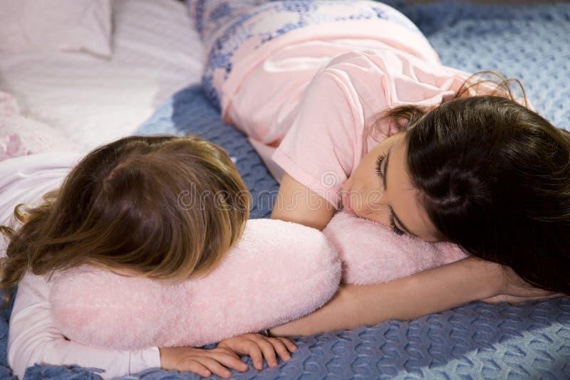 Leuk meisje die in bed met zuster het vertellen geheimen babbelen royalty-vrije stock foto's