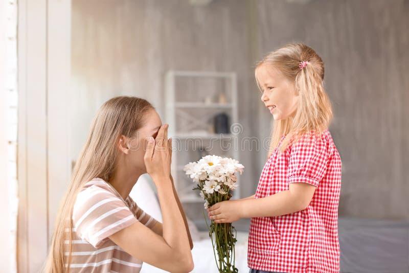 Leuk meisje die bloemen thuis geven aan haar moeder royalty-vrije stock foto's