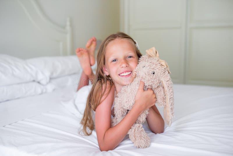 Leuk meisje die camera met haar stuk speelgoed bekijken royalty-vrije stock foto