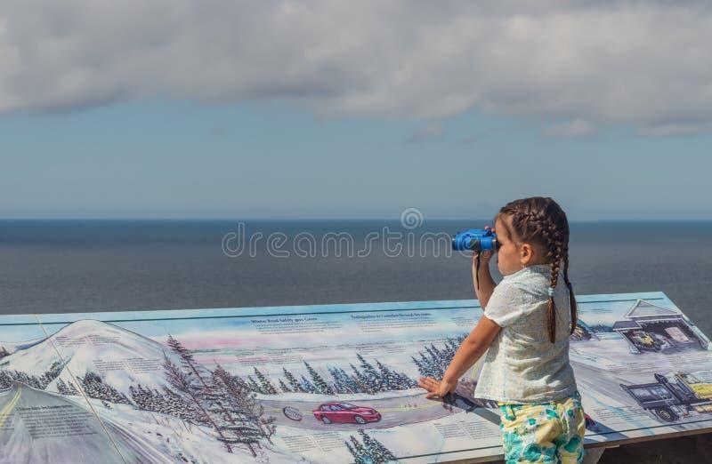 Leuk meisje die de oceaan op Cabot Trail blik-weg bekijken stock foto