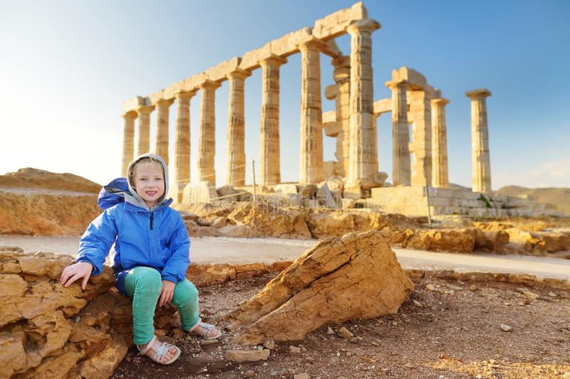 Leuk meisje die de Oude Griekse tempel van Poseidon onderzoeken bij Kaap Sounion, één van de belangrijkste monumenten van de Goud stock foto