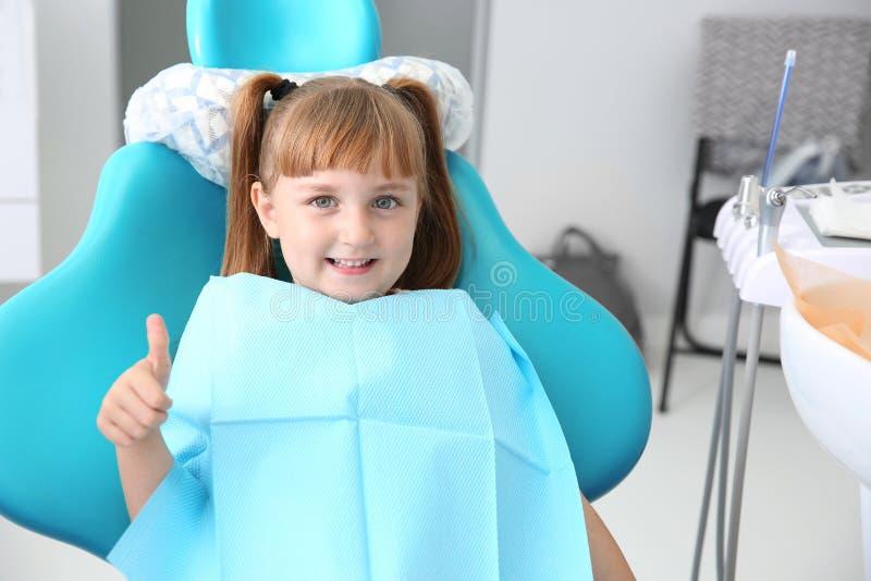 Leuk meisje die duim-op gebaar op het kantoor van de tandarts tonen royalty-vrije stock afbeeldingen