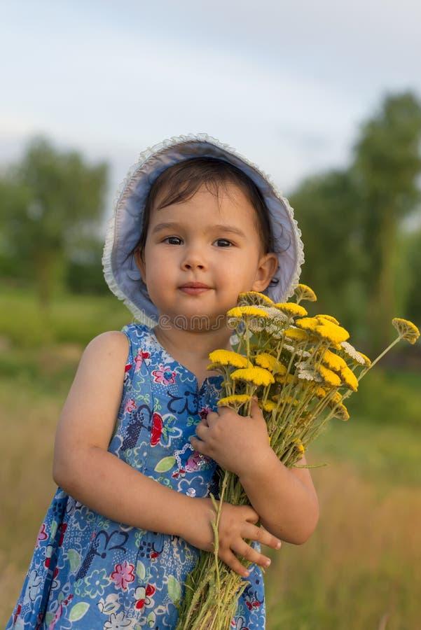 Leuk meisje die een emmer van duizendbladbloemen houden royalty-vrije stock foto