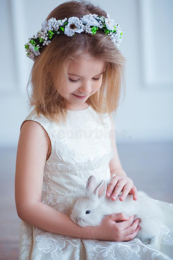 Leuk meisje die een konijntje houden De lente en Pasen-portret van mooi kind met konijn stock foto