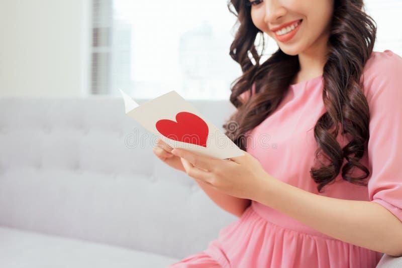 Leuk meisje die een liefdekaart van haar vriend lezen stock afbeeldingen