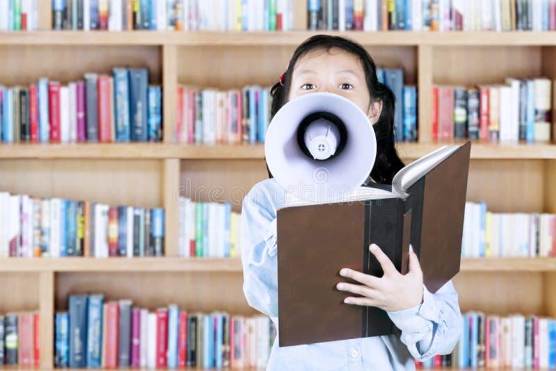 Leuk meisje die een megafoon in bibliotheek met behulp van stock foto's
