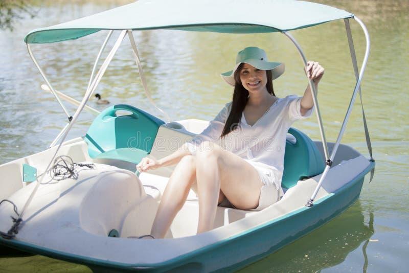 Leuk meisje die een pedaalboot berijden stock foto's