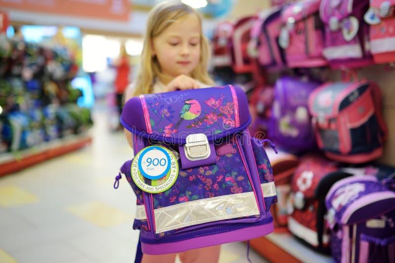 Leuk meisje die een schooltas kiezen alvorens klassen te beginnen Aanbiddelijke leerling het kopen schoolrugzak in een opslag stock fotografie