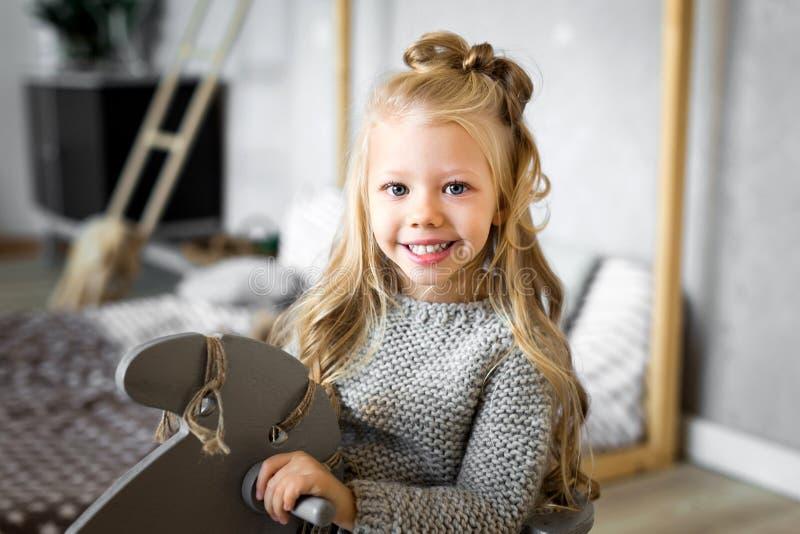 Leuk meisje die een stuk speelgoed paard berijden stock fotografie