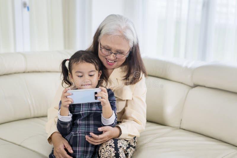 Leuk meisje die een telefoon met haar grootmoeder met behulp van stock foto