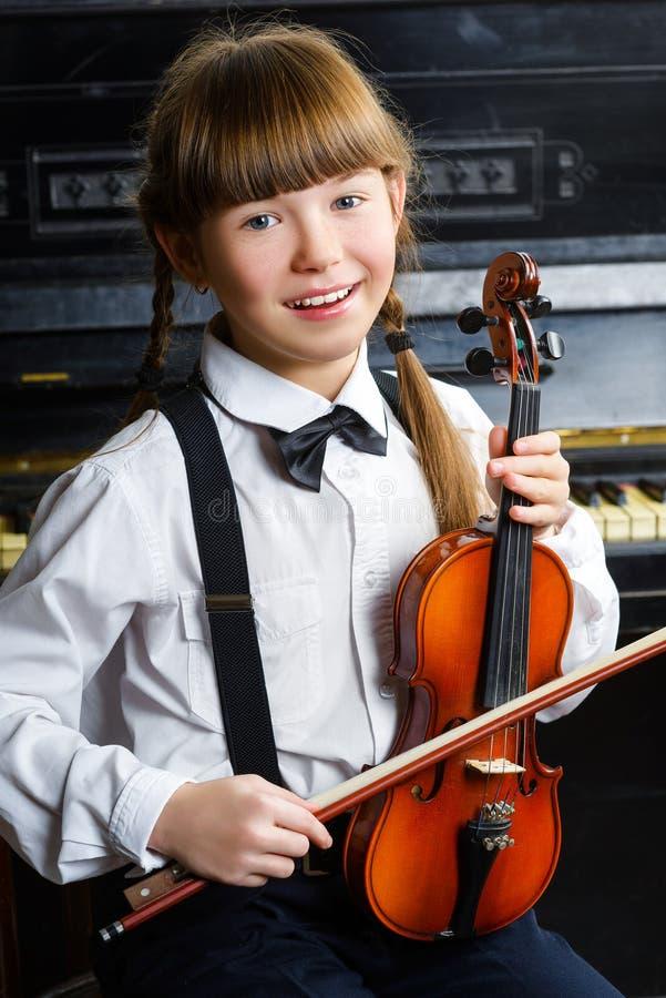 Leuk meisje die een viool binnen houden royalty-vrije stock afbeelding