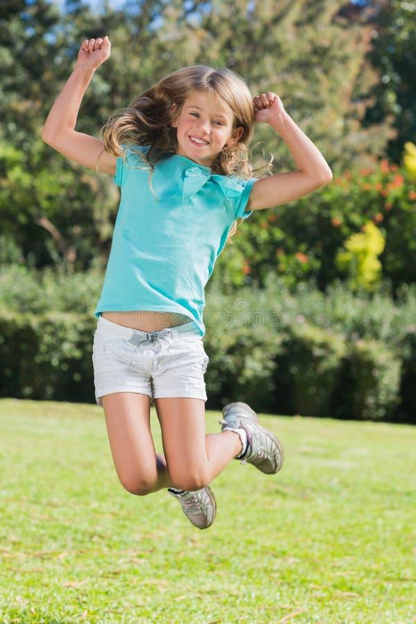 Leuk meisje die en bij camera springen glimlachen royalty-vrije stock afbeelding