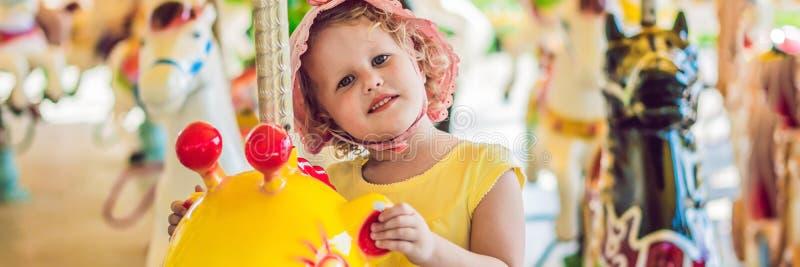 Leuk meisje die in funfair genieten van en op de kleurrijke BANNER van het carrouselhuis, lang formaat berijden royalty-vrije stock foto's