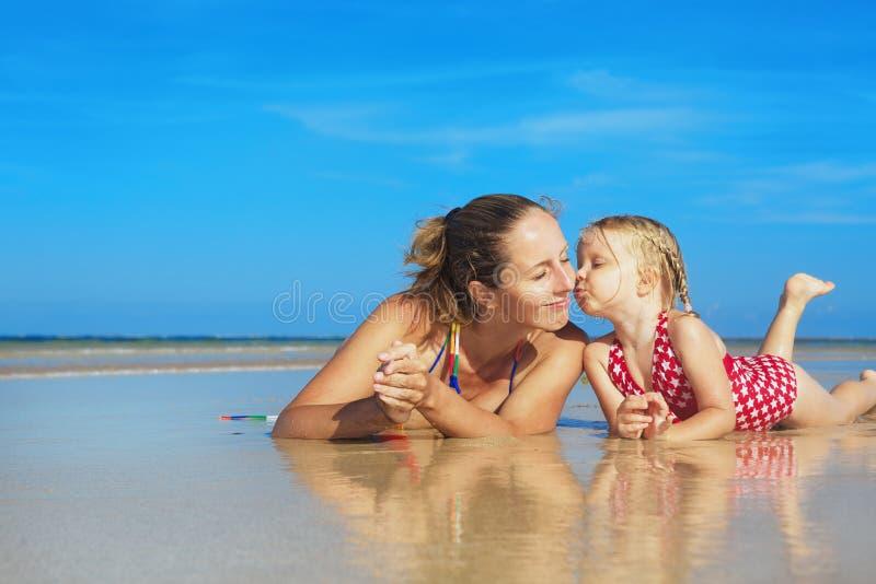 Leuk meisje die gelukkige glimlachende moeder op overzees strand kussen stock afbeelding