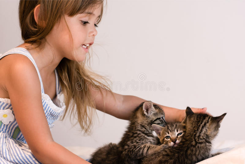 Leuk meisje die 3 gestreepte katkatjes op zacht gebroken wit dekbed helpen royalty-vrije stock afbeeldingen