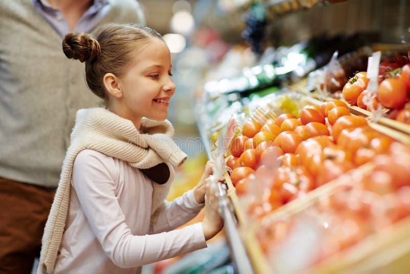 Leuk Meisje die Groenten in Landbouwersmarkt kiezen stock afbeeldingen