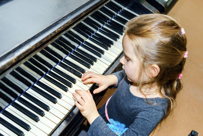 Leuk meisje die grote piano spelen stock fotografie
