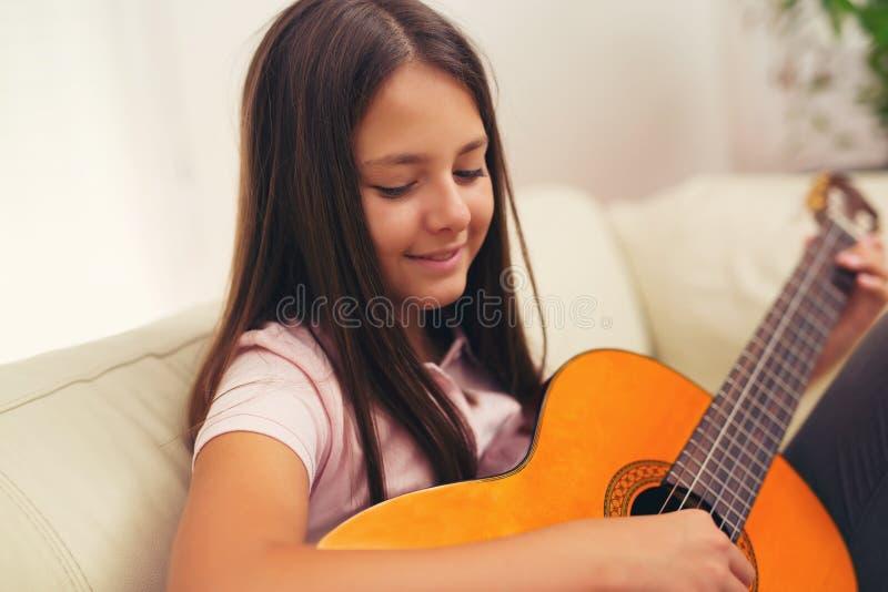 Leuk meisje die haar gitaarlessen uitoefenen royalty-vrije stock afbeelding
