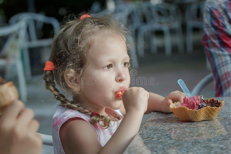 Leuk meisje die haar Italiaanse kegel van het roomijswafeltje eten stock foto's