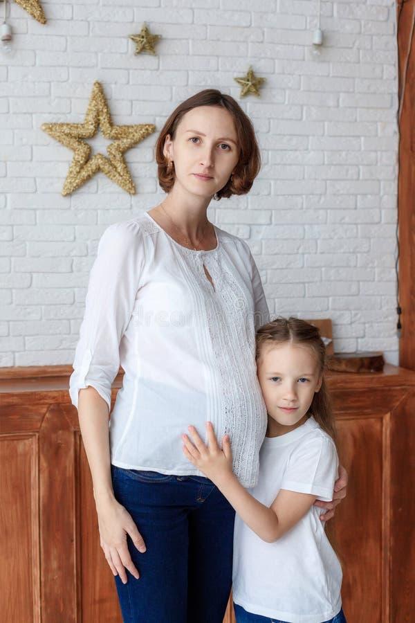 Leuk meisje die haar zwangere moeder in studio koesteren royalty-vrije stock foto's