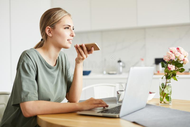 Leuk meisje die in het net doorbladeren terwijl het registreren van voicemail op smartphone stock fotografie