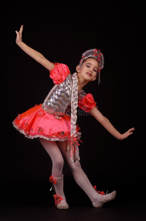 Leuk meisje die inheems Russisch die kostuum dragen op zwarte achtergrond wordt geïsoleerd Zij danst Rotsstijl royalty-vrije stock afbeelding