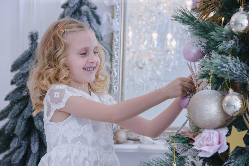 Leuk meisje die Kerstboom verfraaien Kinderen die op het nieuwe jaar wachten stock afbeelding