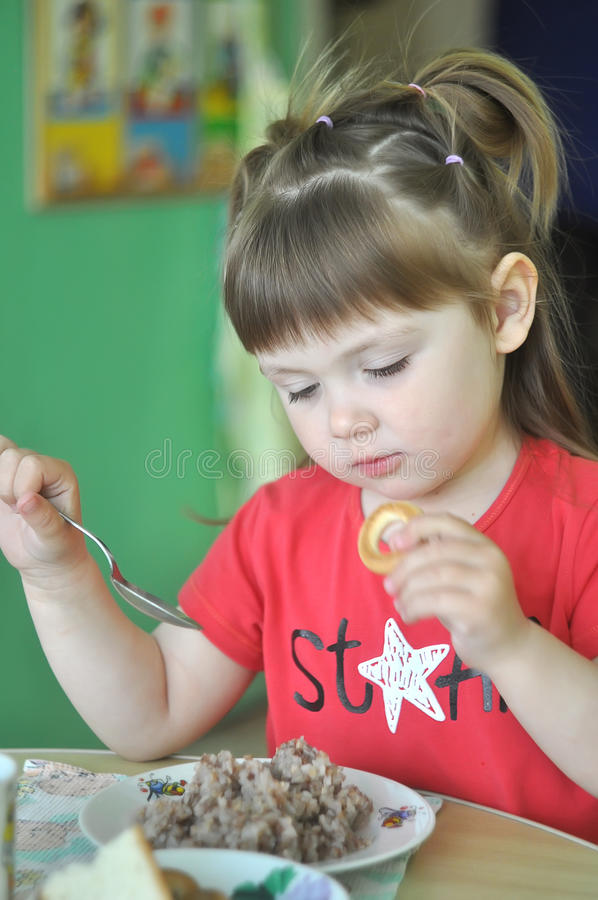 Leuk meisje die in kleuterschool, school eten peuter hebbend havermoutpap voor lunch Kind, babyvoeding, voedsel stock foto's