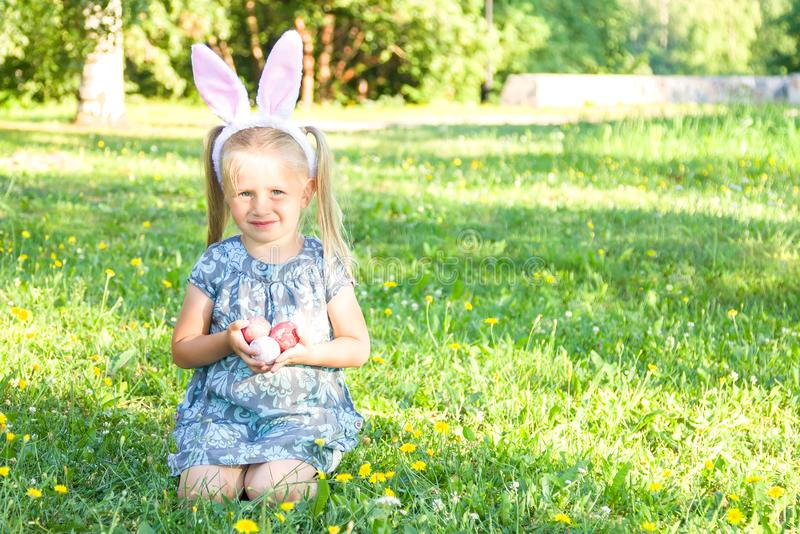 Leuk meisje die konijntjesoren op Pasen-dag dragen Meisjeszitting op een gras en holding geschilderde paaseieren royalty-vrije stock afbeelding