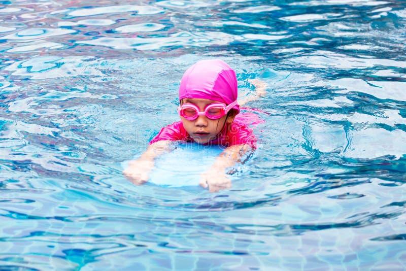 Leuk meisje die met bus bij zwembad leren te zwemmen royalty-vrije stock foto's