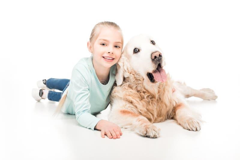 leuk meisje die met golden retrieverhond liggen en bij camera glimlachen royalty-vrije stock afbeeldingen