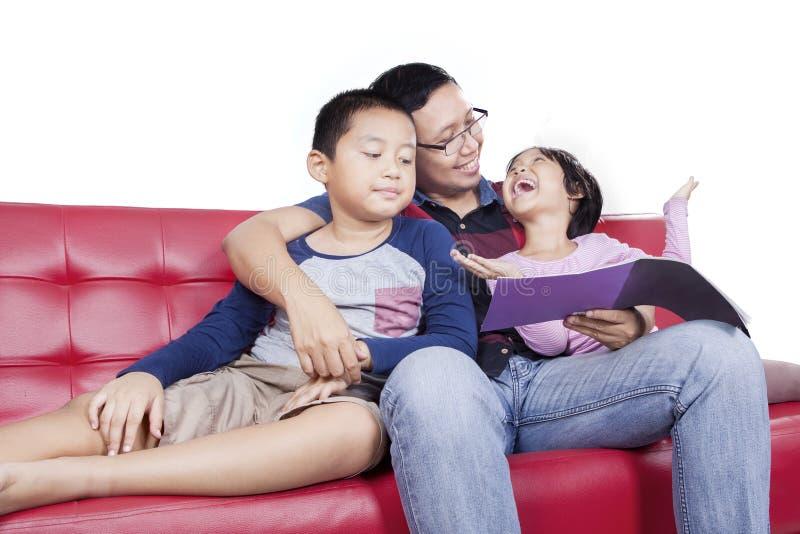 Leuk meisje die met haar papa en broer spreken stock afbeelding