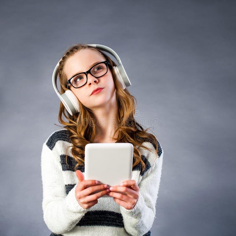 Leuk meisje die met hoofdtelefoons tablet houden stock foto's