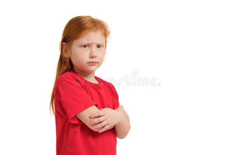 Leuk meisje die met rood haar en gevouwen wapens boze geïsoleerde witte achtergrond kijken stock afbeeldingen