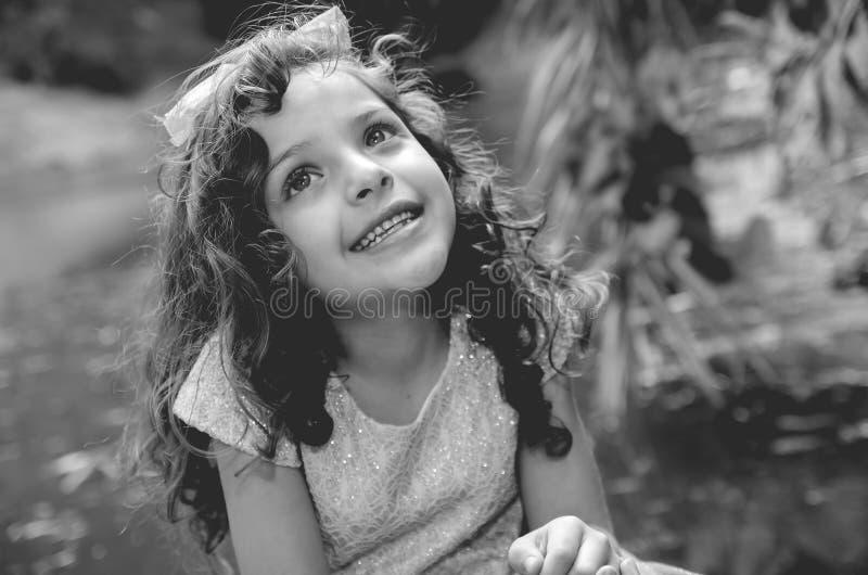 Leuk meisje die mooie blauwe kleding met de aanpassing van hoofdband dragen, die voor camera, in openlucht meerachtergrond stelle stock fotografie