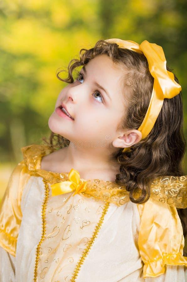 Leuk meisje die mooie gele kleding met de aanpassing van hoofdband dragen, die voor camera, groene bosachtergrond stellen royalty-vrije stock afbeelding