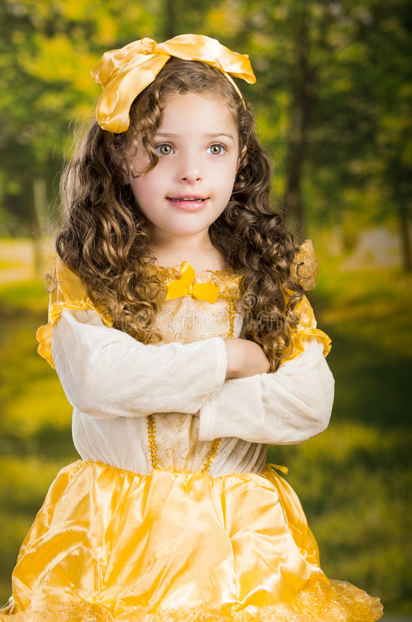 Leuk meisje die mooie gele kleding met de aanpassing van hoofdband dragen, die voor camera, groene bosachtergrond stellen royalty-vrije stock fotografie