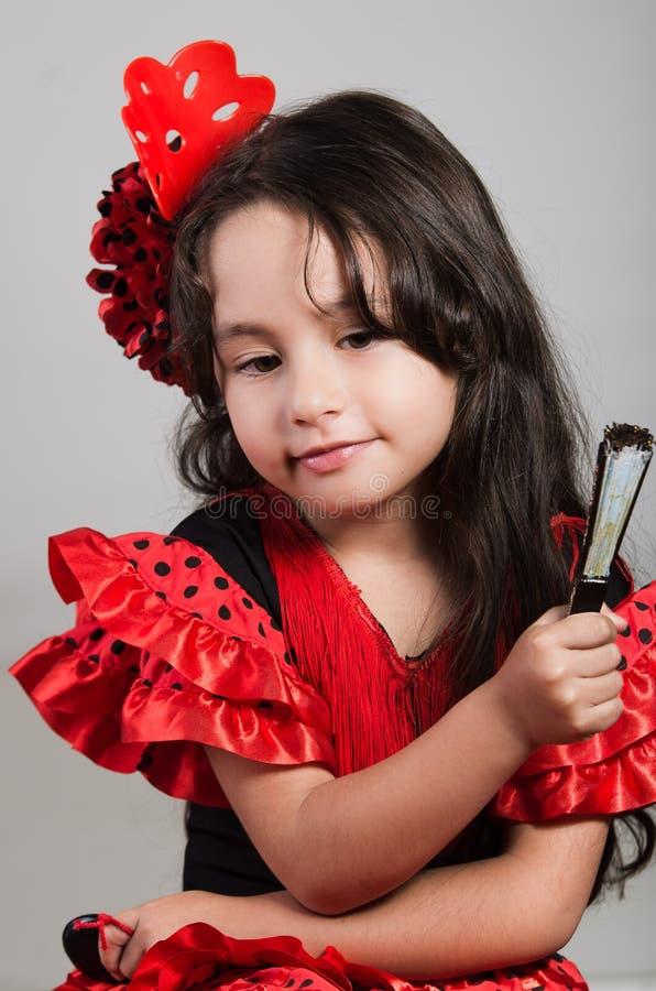 Leuk meisje die mooie rode en zwarte kleding met de aanpassing van hoofdband dragen, die voor camera stellen die Chinese handvent royalty-vrije stock foto's