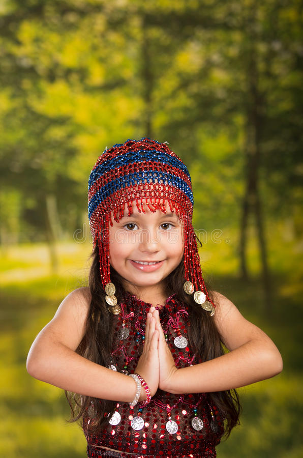 Leuk meisje die mooie rode kleding met de aanpassing van parelhoed dragen, die voor camera, groene bosachtergrond stellen stock foto